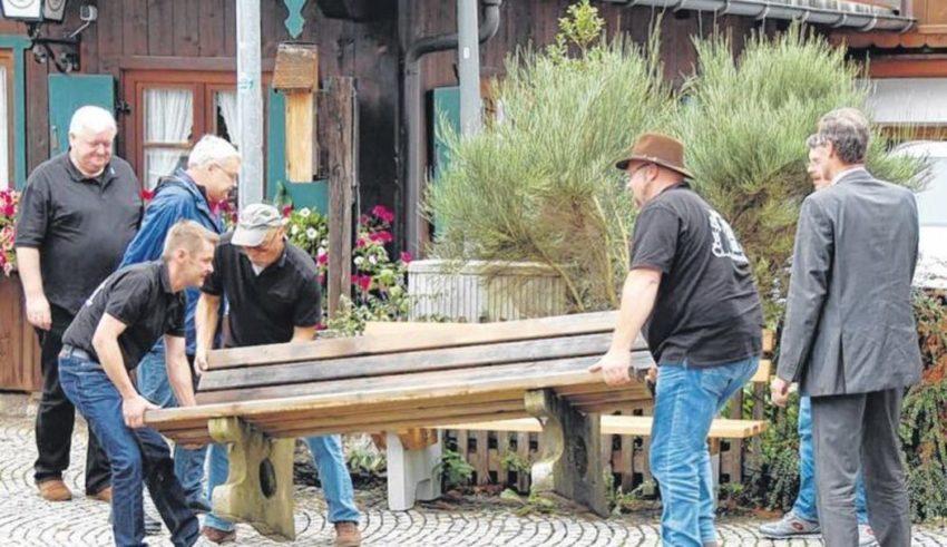 Karl, der Bürgermeister (links), beaufsichtigt seine Vereinskollegen beim Aufstellen der gestifteten Sitzbank. (Foto: Ostermaier)